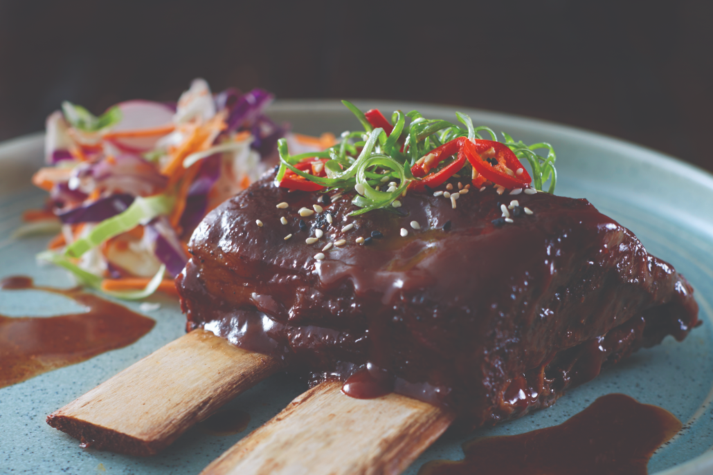Two Beef Ribs placed in the middle of a blue-grey plate with meet sauce, cut up shallots and red chilli's placed on top. A Mixed cabbage salad can be seen towards the back of the plate.